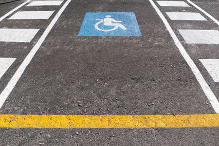 Wheelchair parking space on outdoors. Traffic sign handicapped symbol painted on asphalt