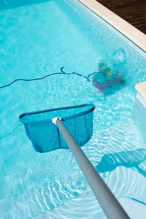 Swimming pool cleaning with Pool Skimmer and underwater cleaning robot 版權商用圖片