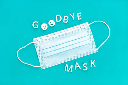 Goodbye mask phrase and face mask isolated on blue background. Concept of no longer be required to wear face masks Standard-Bild