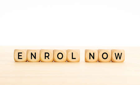 Enroll now phrase in wooden blocks on table. White background. Copy space 版權商用圖片