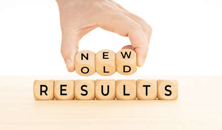 Hand holding New vs old results word in wooden blocks on table. White background. Copy space