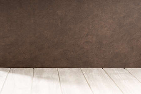 Empty white wooden table and brown textured wall background. Copy space