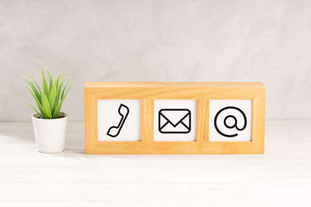 Contact us icons in modern wooden frame on desk. White textured wall. Copy space