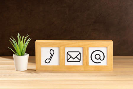 Contact us icons in modern wooden frame on desk. Brown textured wall. Copy space
