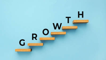 Growth word on staircase on blue background. Increasing business, success process concept. Copy space 版權商用圖片