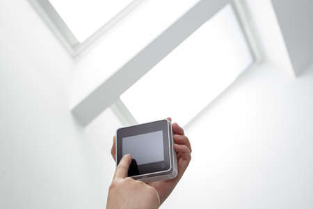 Hand operating a Remote control of a roof windows on indoor. Home automation. Copy space