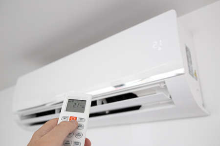 Hand operating a Remote control of a Domestic Air conditioner unit mounted on wall