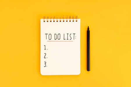 To do list in spiral notepad isolated on yellow background. Top view 版權商用圖片