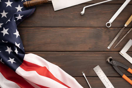 Top view of american flag and work tools on wooden tabletop with copy space. Labor day concept background
