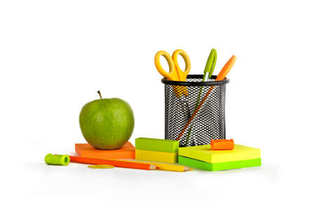 Multicolored stationery set with a green apple on a white background photo