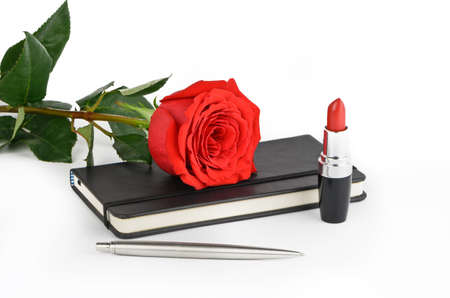 Red rose,  lipstick, black notebook and pen on a light background photo