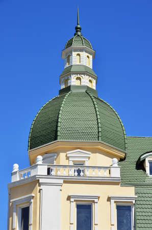 The architectural structure with a green dome on a background of blue sky photo