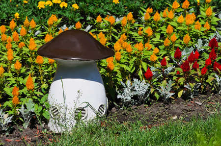 factitious: Large white, artificial mushroom among the bright colors Stock Photo