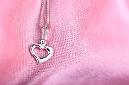 A small, silver heart on pink satin photo