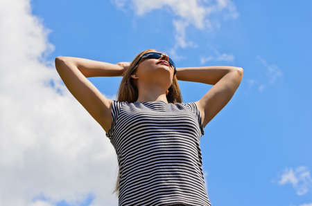 Girl with arms raised in sun glasses on a background of blue sky photo
