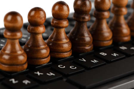 pawns: Group of black pawns on the keyboard closeup Stock Photo