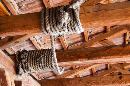Rope wound on a wooden beam at the top Stock Photo