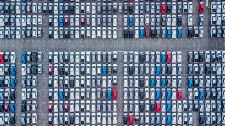 Aerial view new cars lined up in the port for import and export, Top view of new cars lined up outside an automobile factory for import & Export. Stock Photo
