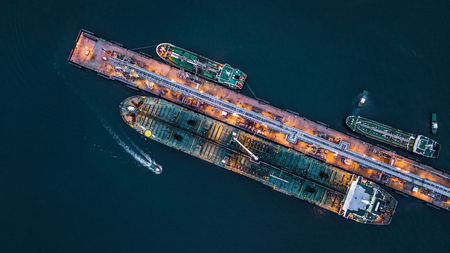 Aerial view of oil tanker ship at the port, Aerial view oil terminal is industrial facility for storage of oil and petrochemical products ready for transport to further storage facilities. Banco de Imagens