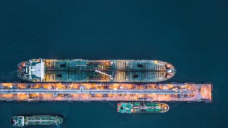 Aerial view of oil tanker ship at the port, Aerial view oil terminal is industrial facility for storage of oil and petrochemical products ready for transport to further storage facilities. Banque d'images
