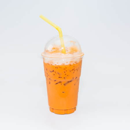 Thai tea in plastic glass on white background, Iced milk tea or Thai milk tea on white background.