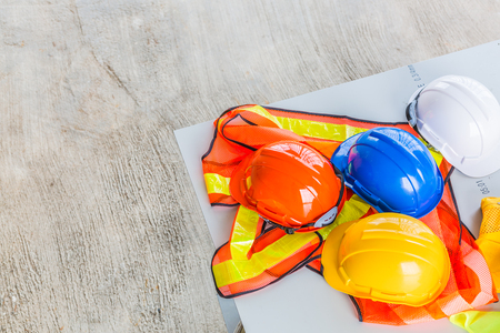 weißer, orange, gelber und blauer Schutzhelmhut mit Sicherheitskleidung für Bauarbeiter für das Sicherheitsprojekt des Arbeiters als Ingenieur oder Arbeiter.