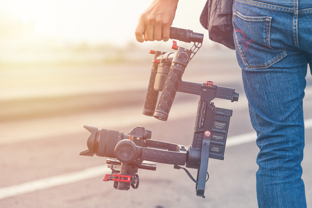 Videographer using camera gimball stabilizer, Professional equipment helps to make high quality video.