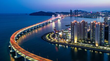 Aerial view Busan Gwangan Daegyo Bridge or Gwangan Bridge skyline and skyscraper building architecture illuminated in the night. Busan, South Korea. Stock Photo