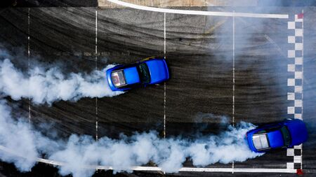 Aerial top view two cars drifting battle on asphalt race track with lots of smoke from burning tires, Two race cars competition drift battle view from above.