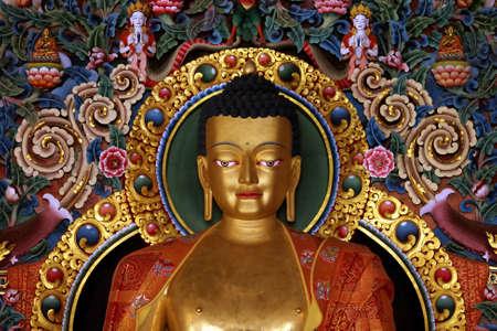 preaching: gilded metal statue of preaching buddha in a tibetan buddhist monastery in chandragiri,orissa, india
