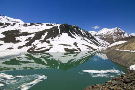 chandratal in summer, half frozen lake between leh and manali photo