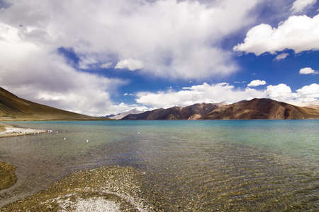 Different colors of Pangong Lake, from clear waters to green and finally blue, with mountains in back side, Ladakh jammu and Kashmir India