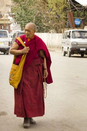 monjes: Ladakh, Jammu y Cachemira, India 20 de julio 2011: un viejo monje caminando en las calles de Leh, Ladakh, Jammu y Cachemira, India Editorial