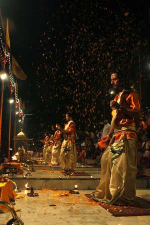 diyas: Varanasi, Uttarpradesh, India, April 1 2011:People throw flowers on the Monks who perform the rituals in Varanasi Ghats, it is like raining flowers