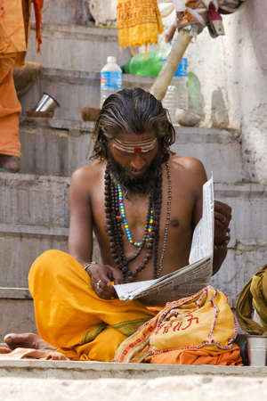 Varanasi, Uttarpradesh, India, April 1 2011:an Indian Sadhu reading a local news paper to keep up with morden times