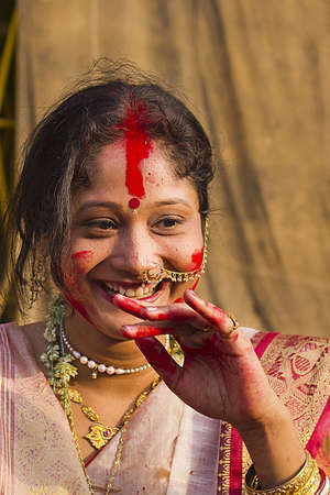 durga: KOLKATA - OCTOBER 10: A Women devotee smiles after appling sindhoor during Durga Puja festival on October 10, 2011 in Kolkata, India.
