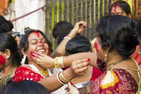 bengali: KOLKATA - OCTOBER 10: A Women devotee apply sindhoor to another