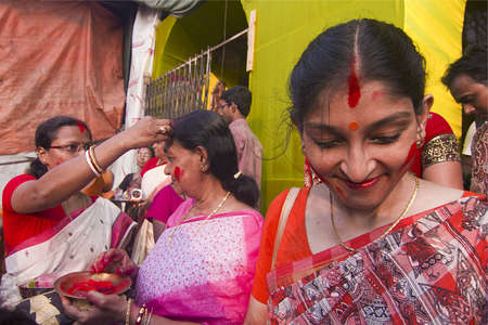 indian saree: KOLKATA - OCTOBER 10: A Women devotee smiles after appling sindhoor or to another Editorial