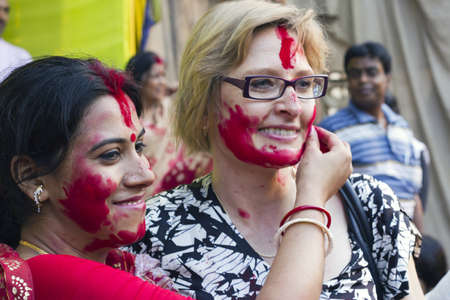 CALCUTTA - OCTOBER 6: A foreign tourist gets a warm cultural greeting with vermilion at Sindur Khela traditional ceremony on the final day of Durga Puja festival on October 6, 2011 in Calcutta, India