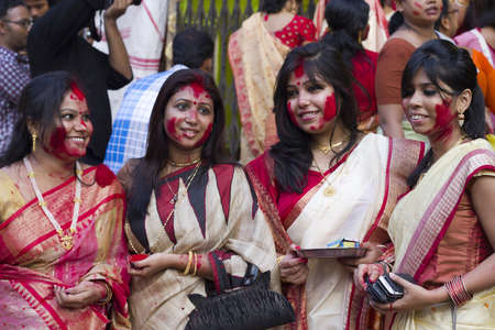 CALCUTTA - OCTOBER 6: Unidentified Hindu women play with vermilion during Sindur Khela traditional ceremony on the final day of Durga Puja festival on October 6, 2011 in Calcutta, India.