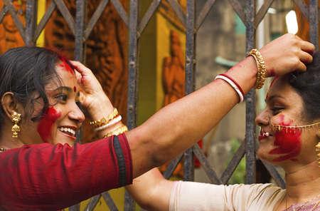 KOLKATA - OCTOBER 10: Two Women devotees applies sindhoor on each other head during Durga Puja festival on October 10, 2011 in Kolkata, India.