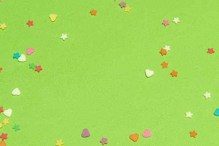 Small colorful candies, Heart and star shapes, on a green background. Valentine day. About love. copy space.