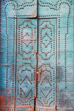 Ancient wooden door with decorative elements and rivets Фото со стока