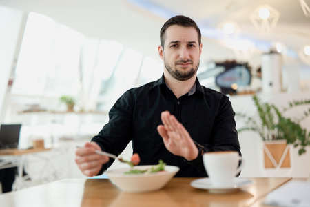 I dont want eat this Young man with beard is upset with the dish the waiter served him. Man is disappointed in his favorite restaurant. Bad food and service concept. Restaurant on the background.