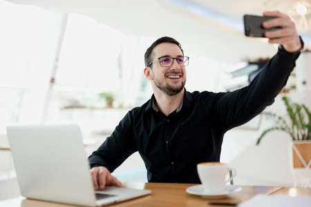 Dont procrastinate Smiling man takes selfie when he should works Concentration problems concept. Man shows to his friends where he works today. Social media cocnept. Light coffeehouse on background.