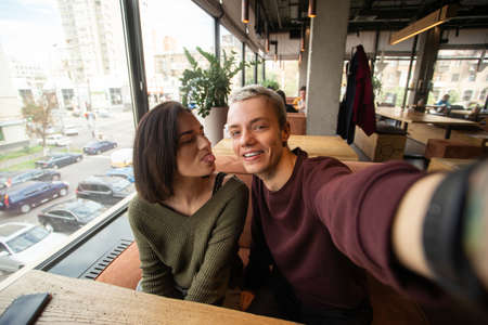 Couple makes crazy faces on camera. Coffee shop on background. Blond man with short hair holds camera and smiling when her girlfriend showing a tongue to him. Stylish man and woman.