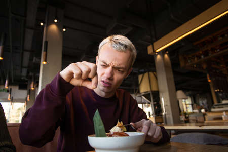 Disgusted young man found hair in his meal at cafe and looks at it with loathing. Bad customer service concept. Blond young man in casual clothes isnt satisfied with the food.