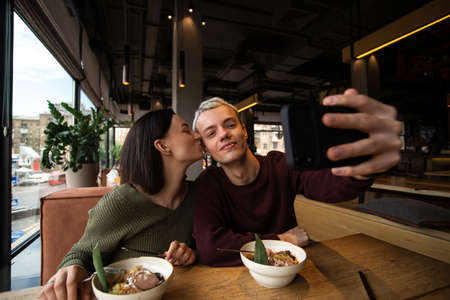 Man and woman in love take photo together in a public place. Attractive brunette woman kisses her boyfriends cheek while he holds smartphone to take selfie. Social media concept. Cafe of restaurant.