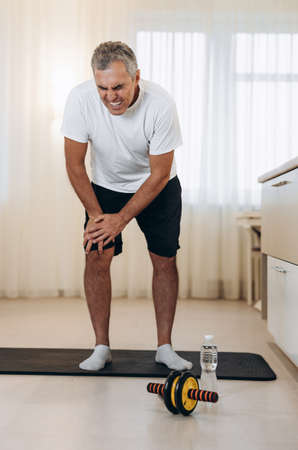 Old man feeling pain in his leg during sport workout at home. Male athlete in black and white sportswear standing on yoga mat and feeling cramps in his right leg.