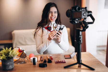Beauty blogger copycat female filming daily make-up routine tutorial on camera. Influencer young woman live streaming cosmetics product review in home studio. Vlogger job. Holding sunglasses